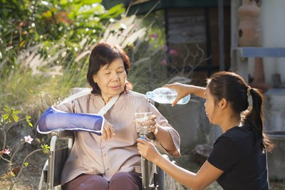 Photo of a young woman pouring a glass of water for an older woman in a wheelchair